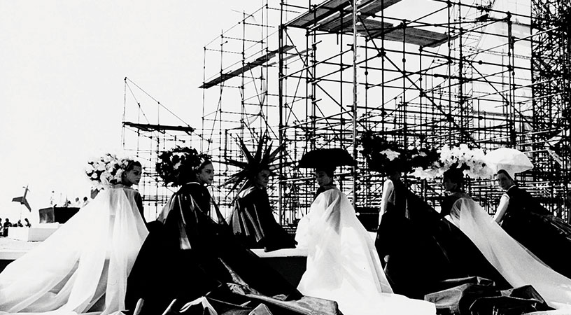 a group of women sit in front of a structure from the film 8 1/2