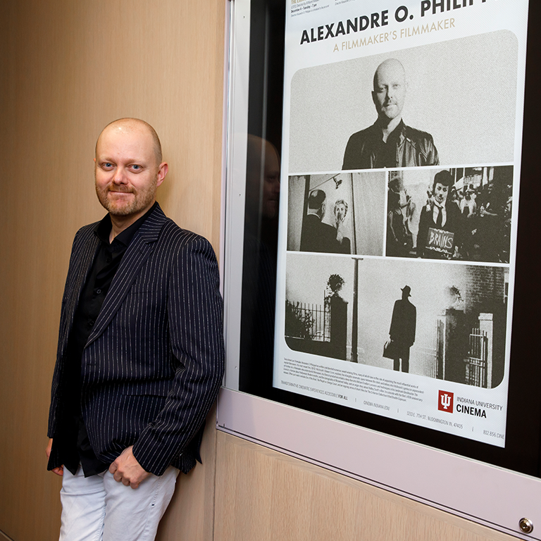 Alexandre O. Philippe stands by the poster for his film series at IU Cinema