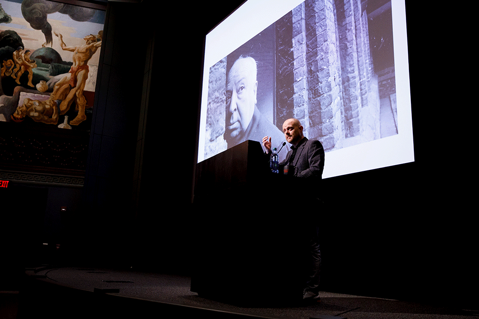 Alexandre O. Philippe on stage with an images of Hitchcock on screen behind him during his Jorgensen Guest Filmmaker program.