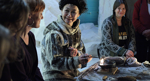 Still image of women sitting around a table from the film Angry Inuk.
