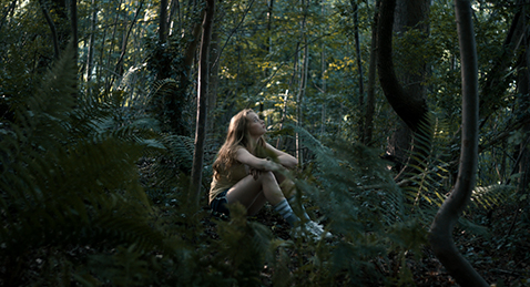 Still image of a girl sitting in the woods from the film Blue My Mind.