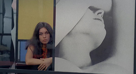 Still image of a women sitting next to a painting from the film Eden and After.