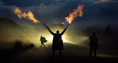 Still image of a man shooting guns in the air at night from the film Five Fingers for Marseilles.