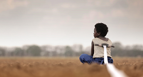 Still image of a girl sitting in a field from the film I Am Not a Witch.