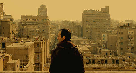 Still image of a man Looking out over a city from the film In the Last Days of the City.