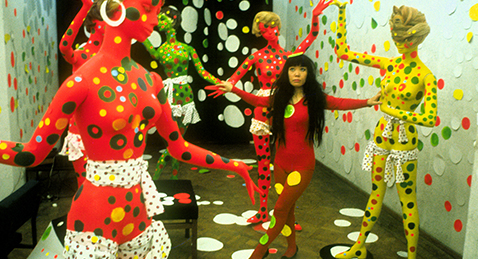 Still image of women dancing in colorful outfit with mannequins from the film Kusama-Infinity.