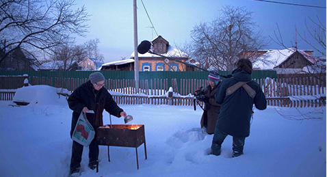 Still image of women cooking in the snow while others play from the film Love is Potatoes.