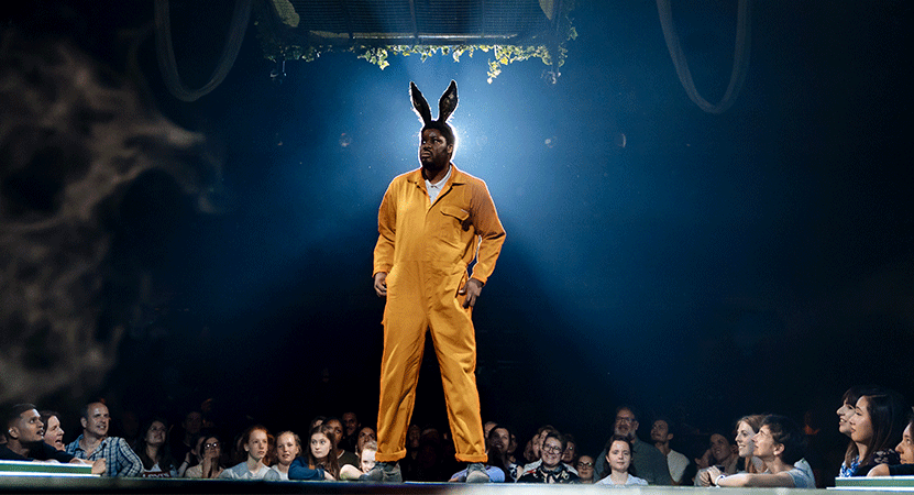 a man in a jumpsuit and bunny ears performs in front of an audience from the national theatre live production of A Midsummer Night's Dream.