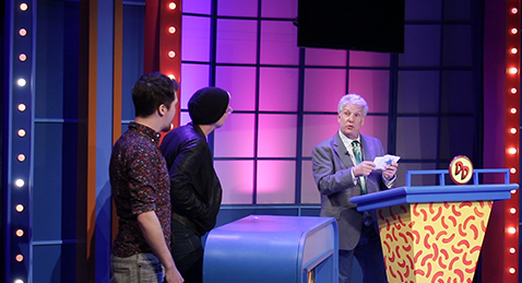 Still image of people competing on a game show from the film On Your Marc.