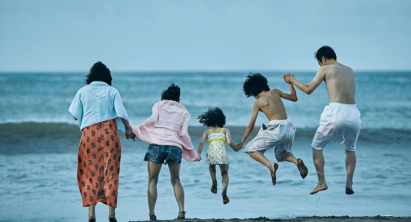 a family jumps in the air on the beach from the film Shoplifters.