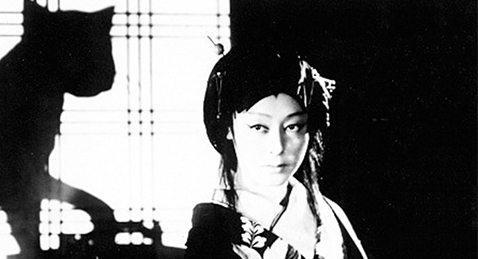 Still image of women with a cat in the background from the film The Ghost Cat and the Mysterious Shamisen.