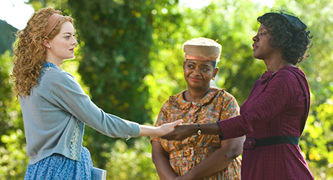 Still image of two women shaking hands while another watching on from the film The Help
