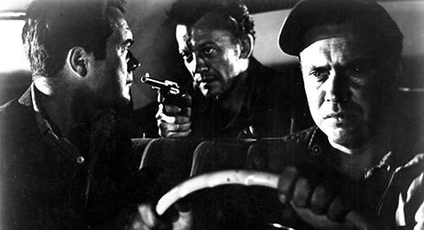 Still image of a man driving a car while the passenger in the front seat is being held at gunpoint by the man in the back seat from the film The Hitch-Hiker.