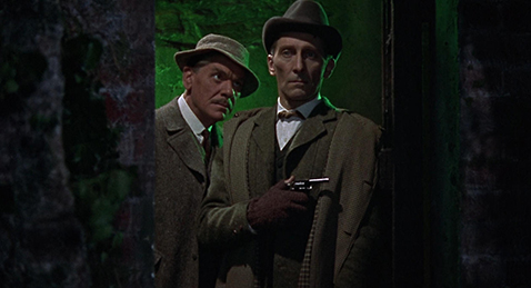 Still image of Sherlock Holmes and Doctor Watson in a dark hallway with a gun from the film The Hound of the Baskervilles.