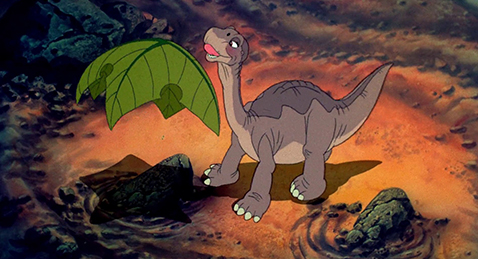 Still image of Littlefoot Getting ready to eat a leaf from the film The land Before Time.