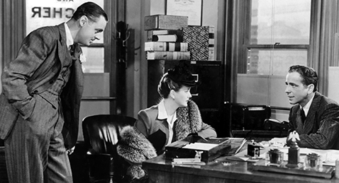 Still image of a man and women sitting at a desk while another man looks on from the film The Maltese Falcon.