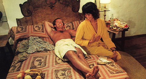 Still image of a man and women laughing in bed from the film The Passenger.
