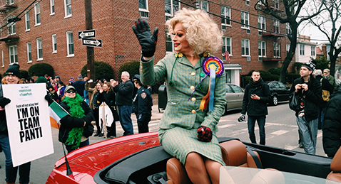 Still image of a queen riding in a convertible in a parade from the film The Queen of Ireland.