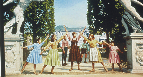 still image of Maria and the von Trapp family singing outside from the film The Sound of Music.
