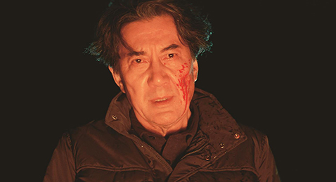 Still image of a man with blood on his face from the film The Third Murder.