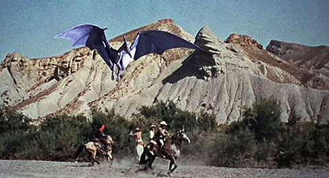 Still image of people on horses being attacked by a dinosaur from the film The Vally of Gwangi.