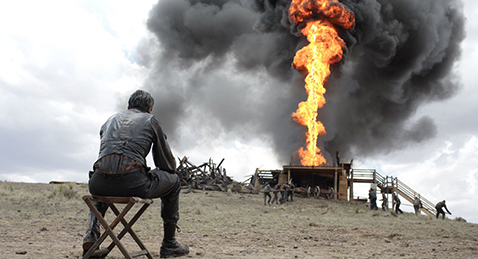 Still image of a man watching as an oil well burns from the film There Will Be Blood.