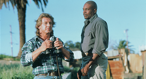 Still image or a man holding binoculars while another man watches form the film They Live.