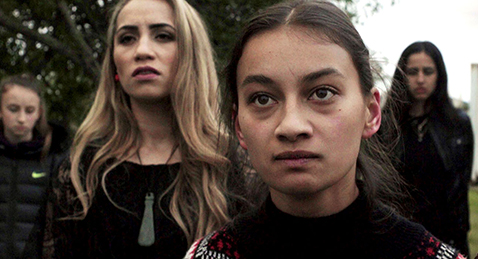 Still image of women looking on with anger from the film Waru.