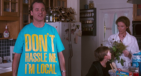 Still image of a mother and son sitting in a kitchen with Bob showing of his new shirt from the film What About Bob?