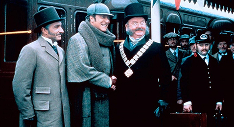 Still image of Sherlock Holmes and Doctor Watson being congratulated next to a train from the film Without a Clue.