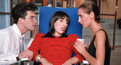 Still image of a women laying in a chair while two other lean over her from the film Women on the Verge of a Nervous Breakdown.