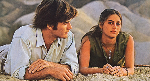 Still image of man and women laying in the sand form the film Zabriskie point.