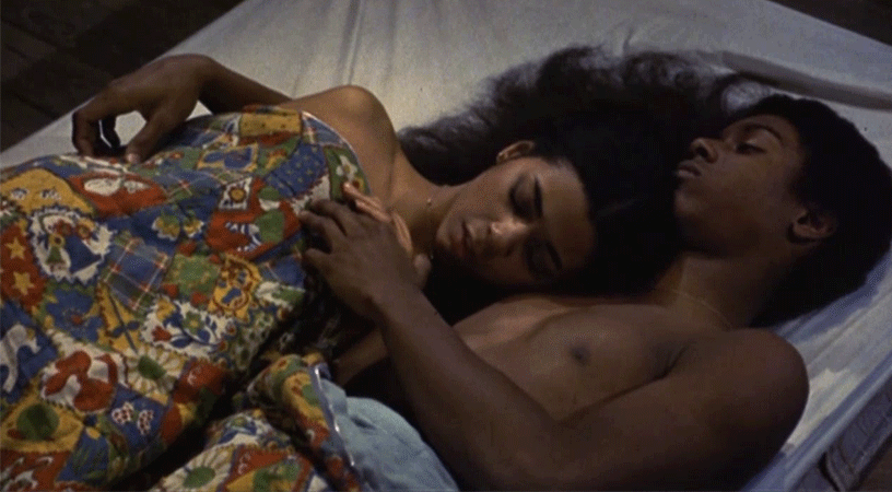 a couple lay in bed from the film Aaron Loves Angela