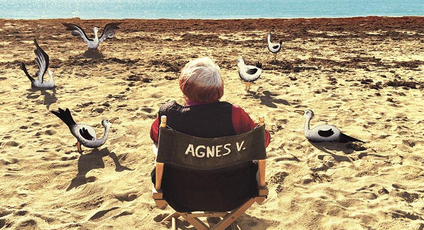 Agnès Varda sits on a beach with animated seagulls from the film Varda by Agnès