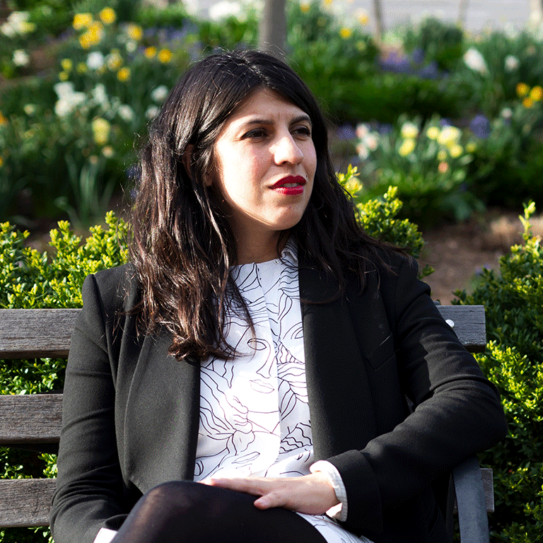 Alejandra Marquez Abella sits on a bench outside IU Cinema.
