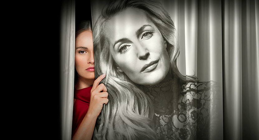 Image of a women peaking from behind a curtain from the national theatre live production of All About Eve.