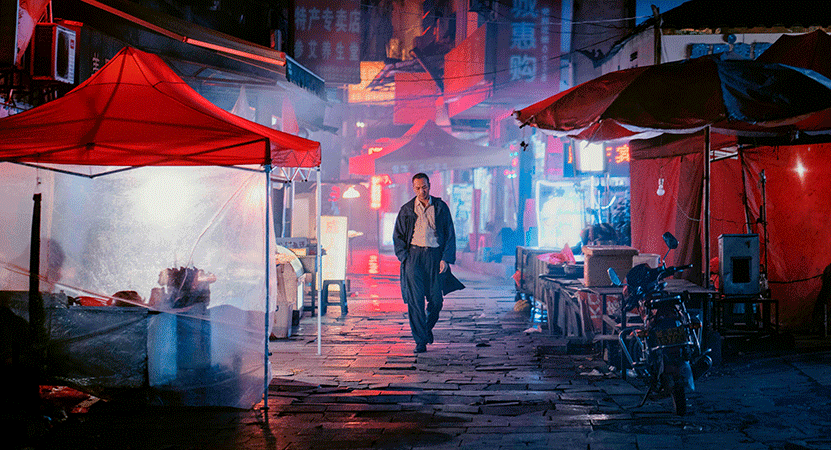 a man walks down a neon lit alley