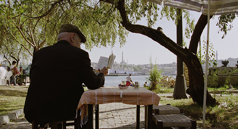 a man sits outside at a table from the film The Edge of Heaven