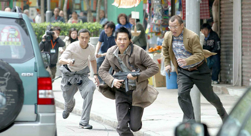 a man with a gun is being chased by two other men with guns from the film Dai Si Gin (Breaking News)