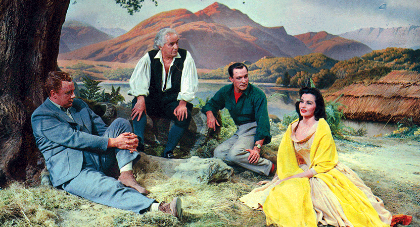 a group of people sit under a tree from the film Brigadoon