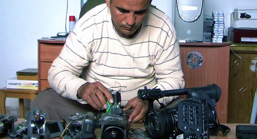 a man works on a camera from the film 5 Broken Cameras