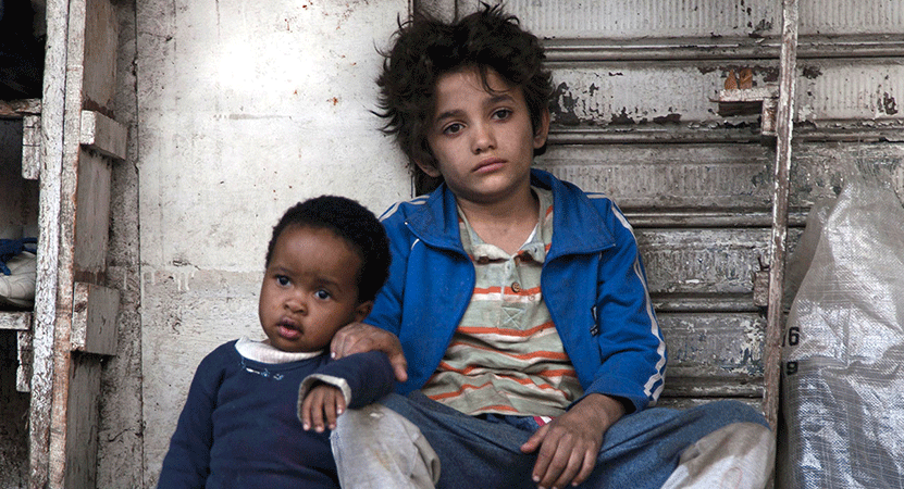 two young children sit on the street from the film Capernaum (Chaos).