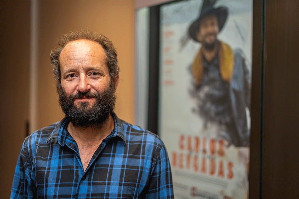 Carlos Reygadas poses in front of the poster for his Jorgensen Filmmaker visit in the lobby of IU Cinema.