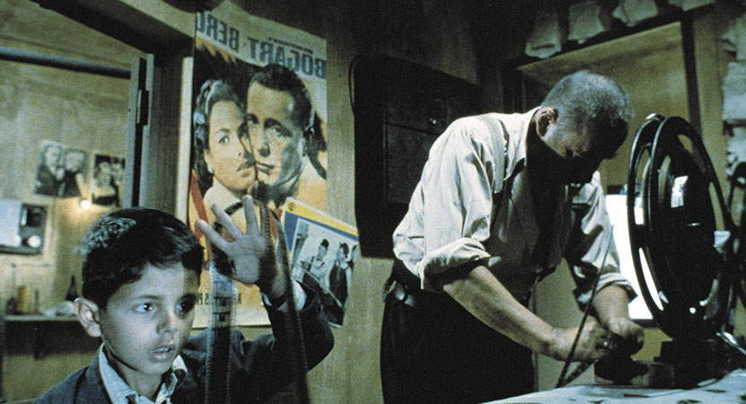 a man and young boy work at a projector from the film Cinema Paradiso
