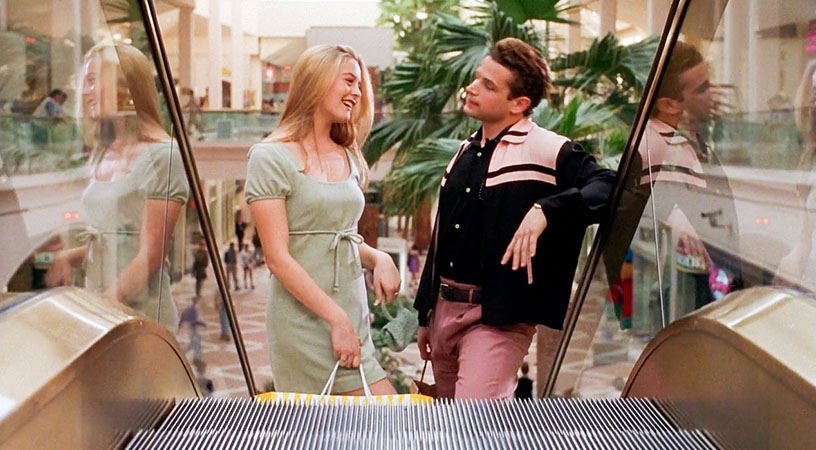 a young man and women ride up an escalator at a man from the film clueless