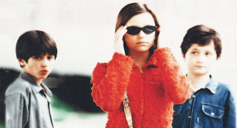 a girl puts on glasses with two boys looking at her from the film Domenica (Sunday).