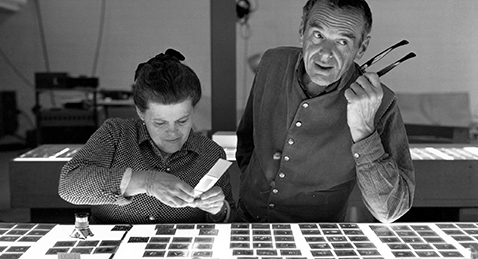 Still image of Charles and Ray Eames looking at photo negatives from the film Eames: The Architect and the Painter.