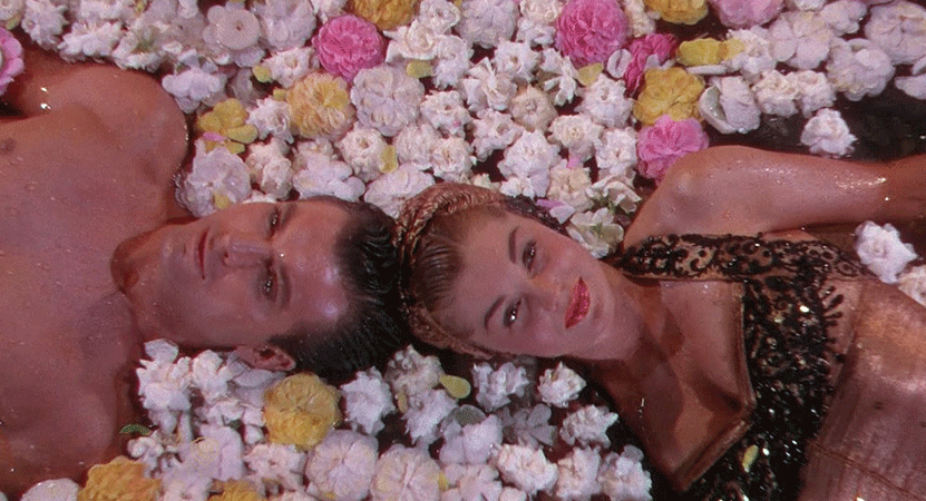 a man and woman lay in flowers from the film Easy to Love.
