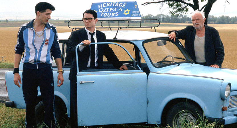 three men stand by a car from the film Everything is Illuminated