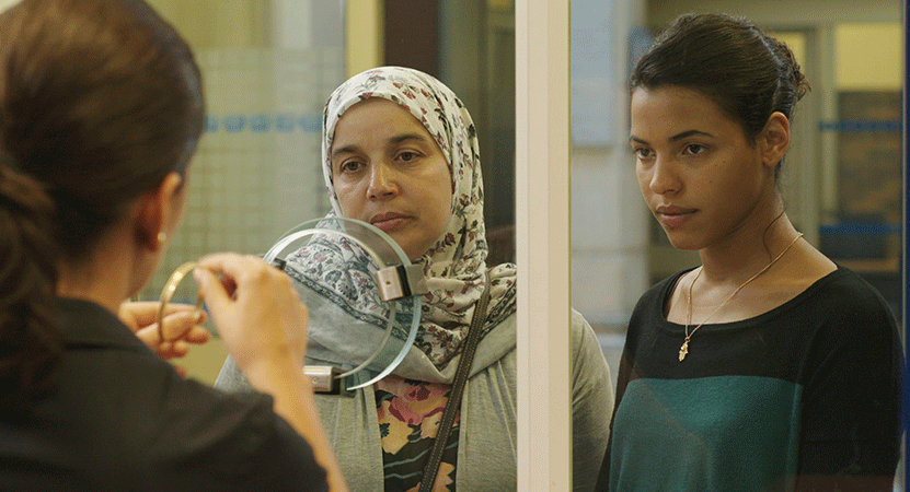 two young women stand at a security window from the film Fatima.